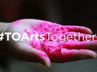 A hand holds pink powder with the text #TOArtsTogether overlaid