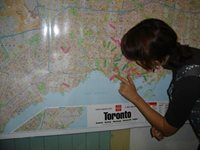 A woman places arrows on a map of Toronto