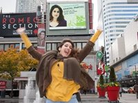 Artist Ghazal Partou jumps in front of her digital billboard in Dundas Square