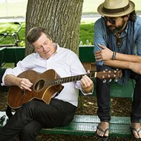 Photo of Mayor John Tory sitting on a park bench playing a guitar. A man sits next to him and watches.