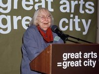 Jane Jacobs stands at a podium