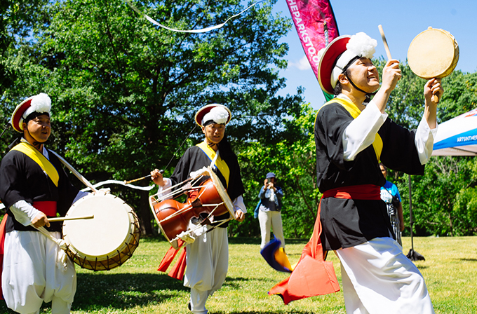 A photo of three musicians from Ensemble Jeng Yi. They are wearing traditional Korean drumming costumes and carrying drums that they are playing.