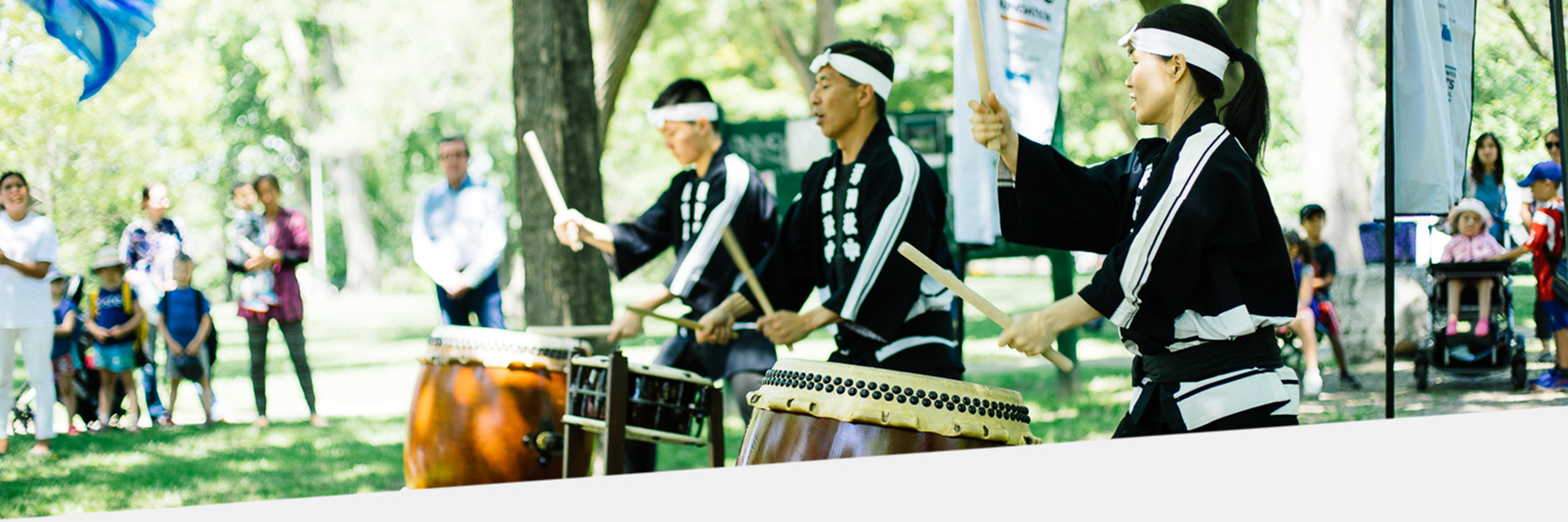 A photo of of three Japanese Taiko drummers in a park. Onlookers watch.